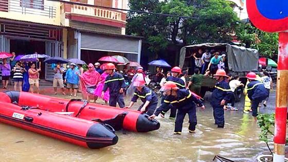 Những người lính cứu nạn cứu hộ trong lũ dữ ảnh 1