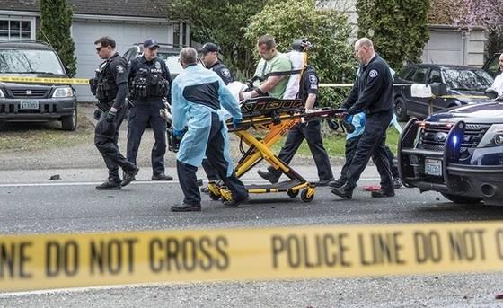 Một người đàn ông được cảnh sát xác định là hung thủ được di chuyển trên băng ca sau khi va chạm với một xe khác. Ảnh: The Seattle Times