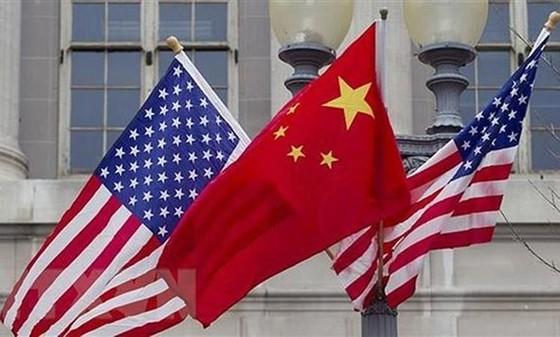 Quốc kỳ Trung Quốc (giữa) và quốc kỳ Mỹ. (Ảnh: Getty Images/TTXVN)