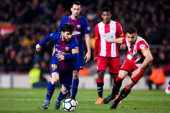 Lionel Messi (trái, Barcelona) đi bóng trước hậu vệ Ginora