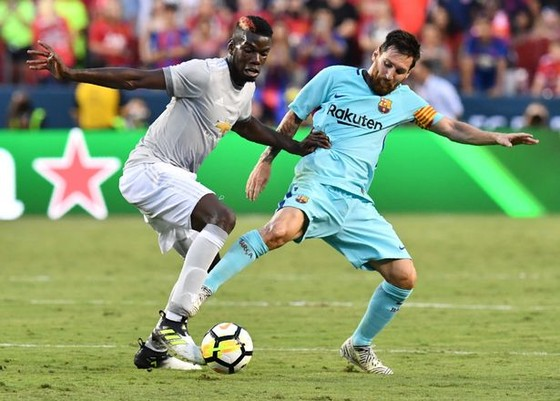 Lionel Messi (phải) tranh bóng với Paul Pogba (Man United)