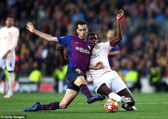 Sergio Busquets tranh bóng với Paul Pogba (phải)
