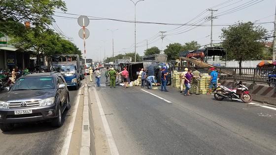 Xe tải lật giữa QL1, người dân cùng CSGT dọn hàng trăm thùng nước ngọt giúp tài xế ảnh 2