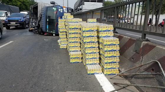 Xe tải lật giữa QL1, người dân cùng CSGT dọn hàng trăm thùng nước ngọt giúp tài xế ảnh 1