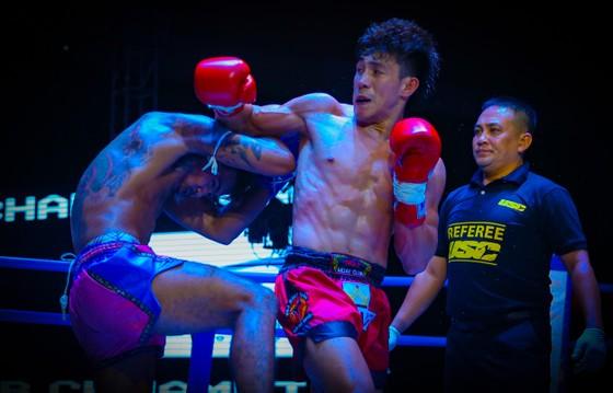 Võ sĩ Duy Nhất (đỏ) trong pha ra đòn đánh bại đối thủ Thái Lan Phimwong Kitty. Ảnh: Dũng Phương
