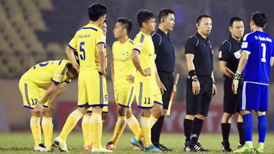 Thủ môn Nguyên Mạnh (bìa phải) và các cầu thủ SLNA phản ứng tổ trọng tài. Ảnh: Minh Hoàng