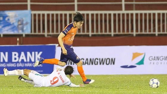 Xuân Trường đi bóng vượt qua cú chùi bóng của tiền vệ Văn Thanh. Ảnh: DŨNG PHƯƠNG