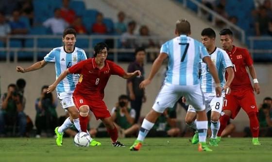 Tuấn Anh trong vòng vây của các cầu thủ Argentina