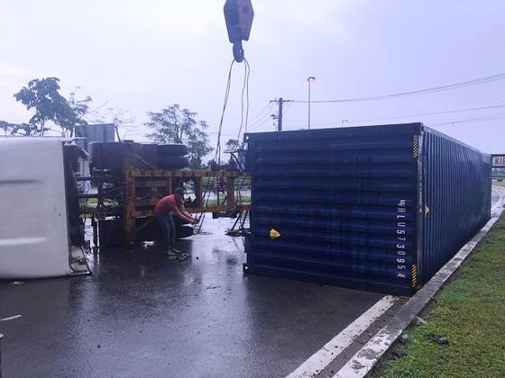 Xe container ôm cua lật chắn ngang đường trong cơn mưa ảnh 2