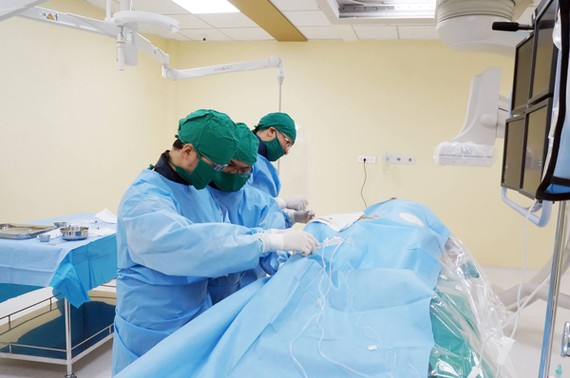 Doctors perform the operation on the elderly woman to palce stent (Photo: SGGP)