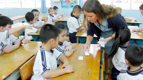 Foreign teacher teach Maths to kids in the program (Photo: SGGP)