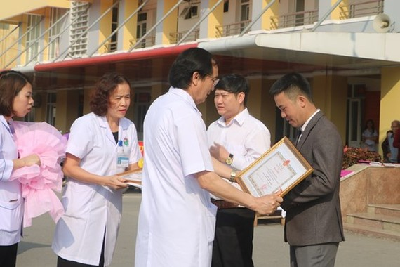 Dr. Nguyen Viet Dong gives certificates of merit to two donors (Photo: SGGP)