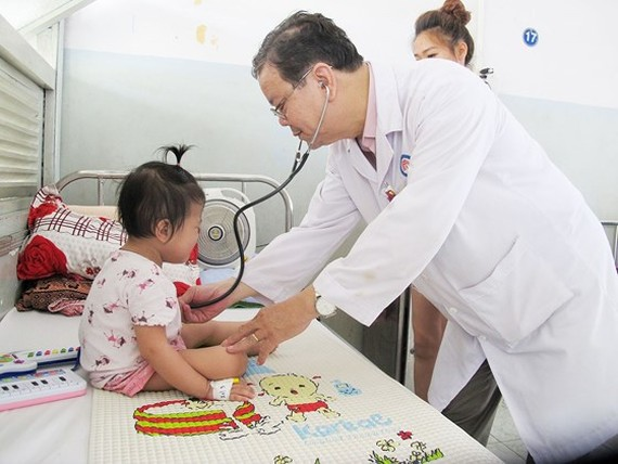A medical worker is examining a tuberculosis kid in Pham Ngoc Thach hopital (Photo: SGGP)