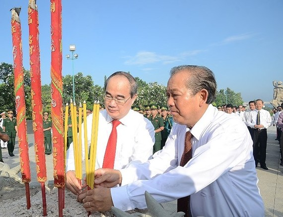 Politburo member and Standing Deputy Prime Minister Truong Hoa Binh (R) and Politburo member and Secretary of the Ho Chi Minh City Party Committee Nguyen Thien Nhan offer incense to heroic martyrs (Photo: plo.vn)