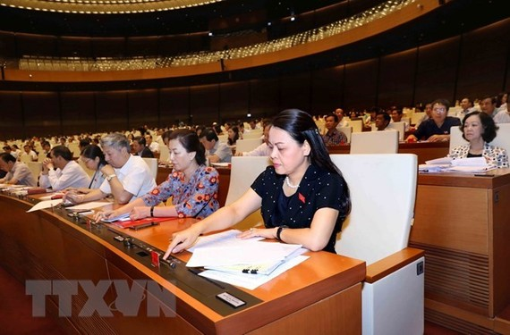 National Assembly deputies press the vote button to pass the resolution on the programme of building laws and ordinances in 2019 (Photo: VNA)