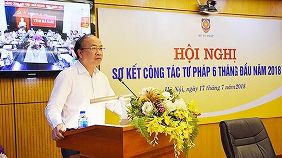 Deputy Minister of Justice Phan Chi Hieu is presenting his report in the meeting