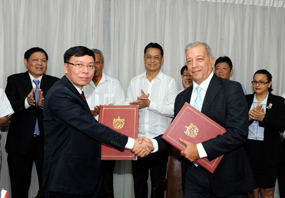 Representatives of the General Department of State Reserves of Vietnam and the Cuba Food Import-Export Corporation exchange the signed document on the handover of the 5,000 tonnes of rice (Photo: VNA)