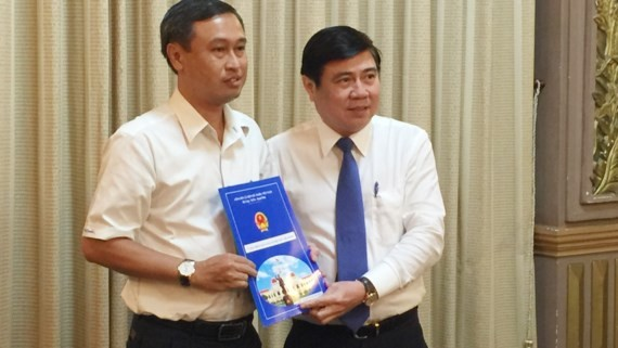 Chairperson of HCMC People's Committee  Nguyen Thanh Phong (R)  gave the appointment decision to Mr. Huynh Thanh Nhan