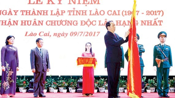 President Tran Dai Quang attaches the First class Independence Medal on traditional flag of Lao Cai province.