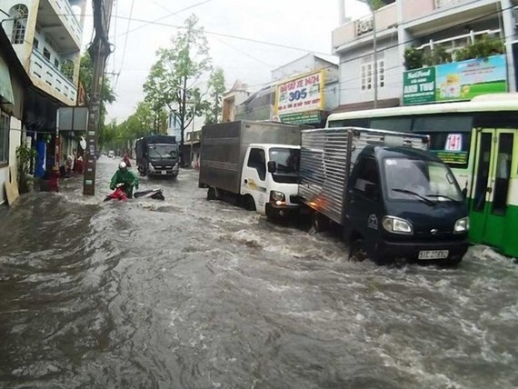 Drivers struggle to deal with flooding caused by heavy rains in HCM City. (Photo: VNA)