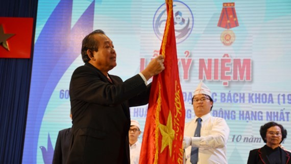 Deputy Standing Prime Minister Truong Hoa Binh offers the First Class Labor Medal of the Vietnamese President to the university's leaders.