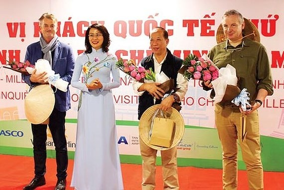 Deputy Chairwoman of  Ho Chi Minh City People's Committee Nguyen Thi Thu offers flowers to the five millionth international visitor to Ho Chi Minh City at the welcoming ceremony
