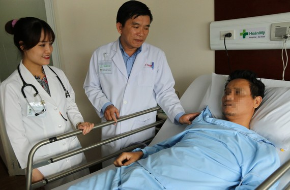  Bác sĩ Cao Minh Thông thăm khám bệnh nhân sau phẫu thuật.