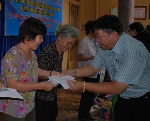 溫陵會館理事長張子諒向長者贈送扶助金。