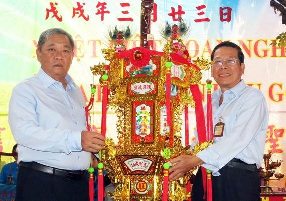 崇正會館理事長鄭鑫發(左)把第一盞 聖燈交給陳添祥先生。