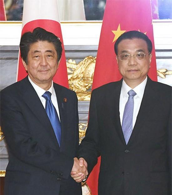 在會談前握手的日本首相安倍晉三和中國國務院總理李克強。(圖源: 日本經濟新聞)