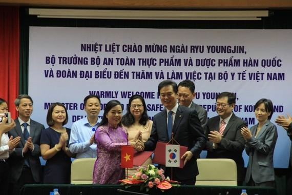 衛生部長阮氏金進(前左)與韓國食品藥品安全部部長Ryu Young-jin簽署合作備忘錄。(圖源:阮顯)