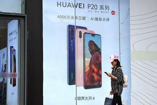 福州市民從華為手機廣告旁經過。
