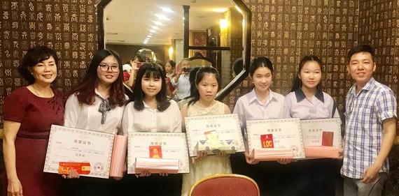 光芳盛股份有限公司郭虹(左一)和曾廣健(右一)代表三有實業貿易有限公司關達賢特向獲獎學生作出獎勵。