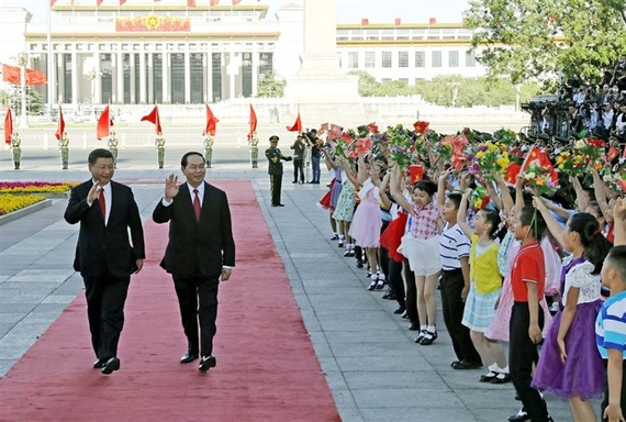 President Tran Dai Quang (right) and Party General Secretary and President of China Xi Jinping attend a welcoming ceremony outside the Great Hall of the People in Beijing, China on Thursday. (Photo: VNA/VNS)