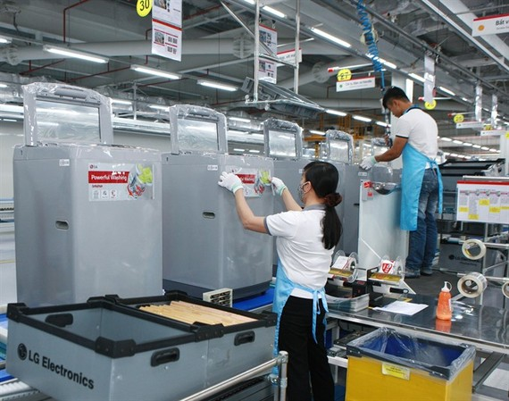 Employees of LG Electronics Vietnam, a Korean-invested firm, operate a production line at the firm's factory in Hanoi. (Photo: VNA/VNS)