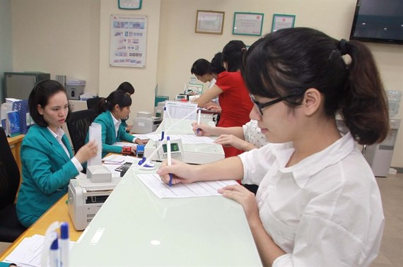 Customers make transactions at ABBank branch office in Thai Binh Province. (Photo: VNA)