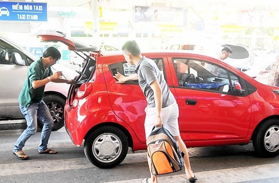 An Uber taxi cab picks up passengers in HCMC (Photo: SGGP)