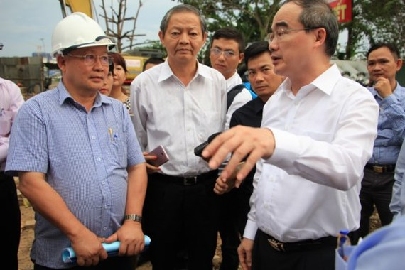 HCMC party chief Nguyen Thien Nhan and city People's Committee deputy chairman Le Van Khoa survey the pump system installation area in Nguyen Huu Canh street on July 12 (Photo: SGGP)