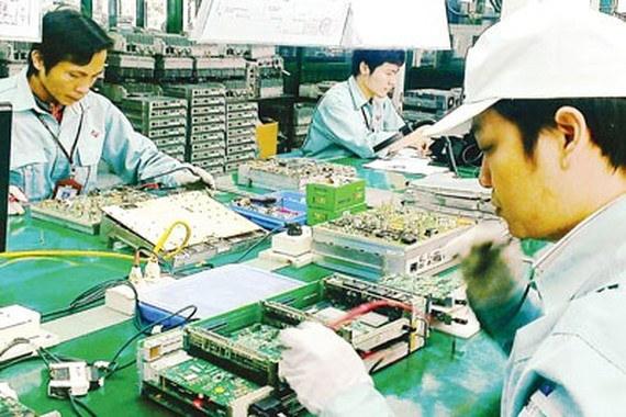 Workers making telecoms equipment at a plant of Viettel, a state-owned enterprise operated by the Ministry of Defense (Photo: SGGP)