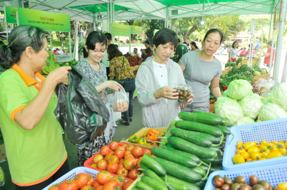 Residents buy safe farm produce at the safe farm produce fair at Le Thi Rieng park on September 24 (Photo: SGGP)