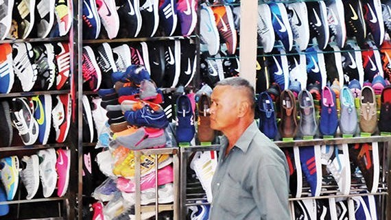 Shoes faking famous brand names are sold rampantly in the market (Photo: SGGP)
