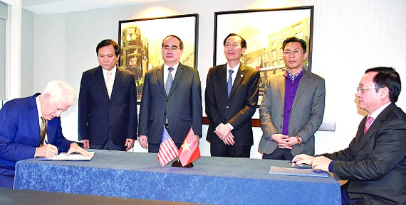 Director of HCMC National University Huynh Thanh Dat (R) and Principle of UCLA Gene D.Block sign a cooperation agreement in Washington D.C. on December 17 (Photo: SGGP)