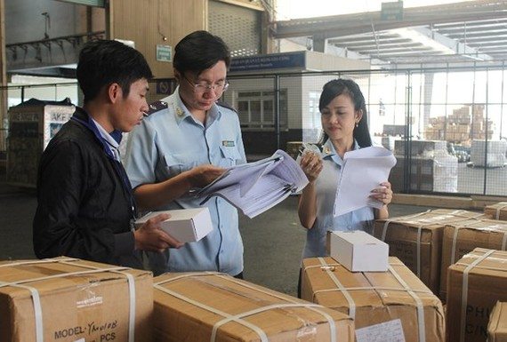 Customs officials examine a consignment of goods at a seaport in HCMC (Illustrative photo: SGGP)
