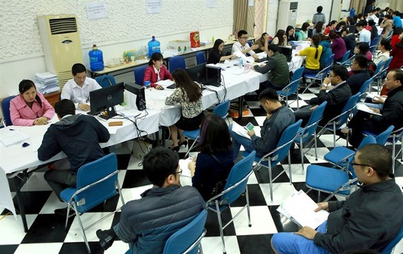 People wait for their turn to complete tax procedures at the Hanoi Tax Department.(Photo: VNA/VNS)