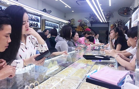 Customers buy gold at a jewelry shops in An Duong Vuong street, District 5 on February 25, a day before God of Wealth Day (Photo: SGGP)
