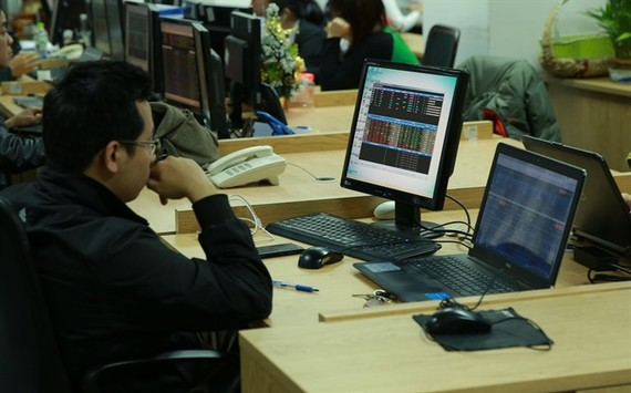 Investors watch market movements at the Military Bank Securities (MBS) trading floor. (Photo: VNS)