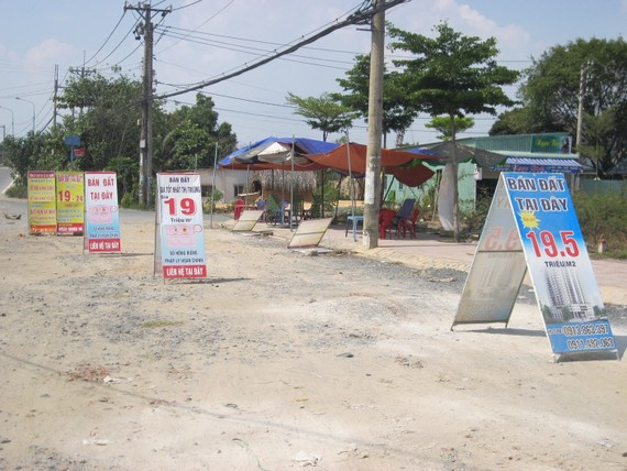 Boards offering property projects for sale in Nguyen Xien street, District 9 (Photo: SGGP)