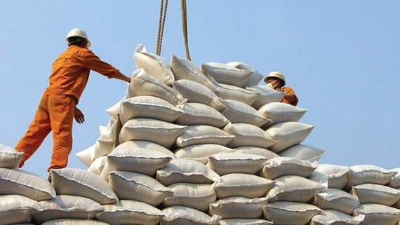 Workers pile up rice bags