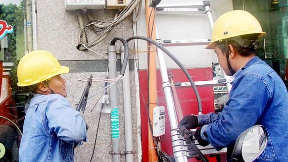 Thi công đấu nối từ hệ thống điện nổi sang hệ thống điện ngầm cho người dân trên đường Võ Thị Sáu. Ảnh: BẢO NHƯ