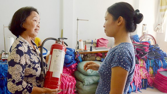 Cô Bùi Thị Khánh, Trưởng khu phố 13, phường 12, quận Gò Vấp, hướng dẫn người dân sử dụng bình chữa cháy